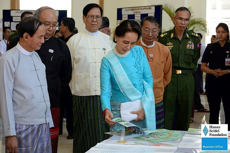 Daw Aung San Su Kyi looking at parliament related publications by the Hanns Seidel Foundation