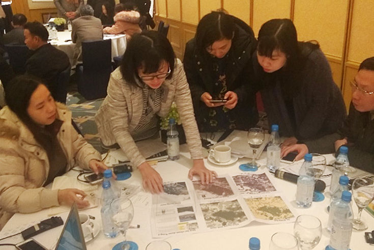 Mrs Nguyen Thu Trang explains the dynamics of the simulation game to a group of representatives of Quang Nam and Ha Tinh province